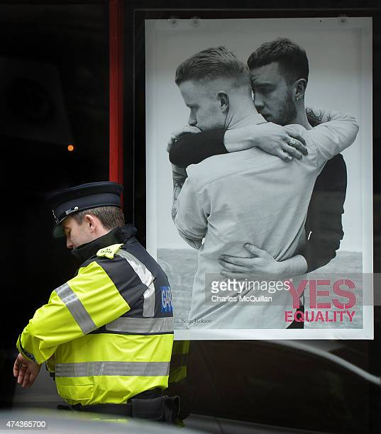 Garda police officer checks his watch beside a poster promoting the Yes campaign in favour of samesex marriage on May 22 2015 in Dublin Ireland...