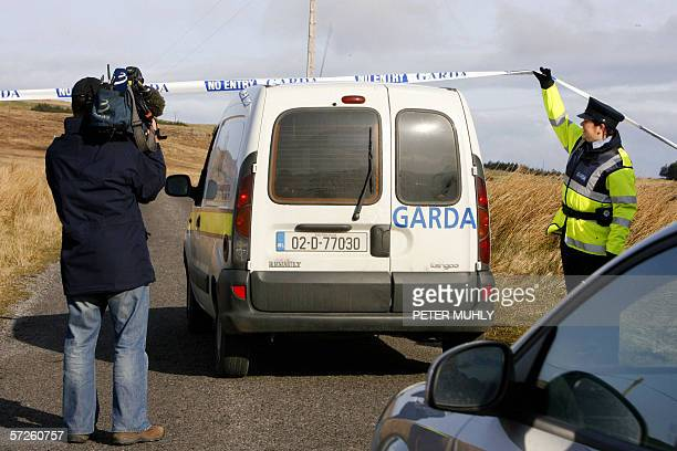 Garda police officers allow a Garda vehicle to pass along a road leading to a remote house in Glentise Co Donegal Ireland of Denis Donaldson 05 April...