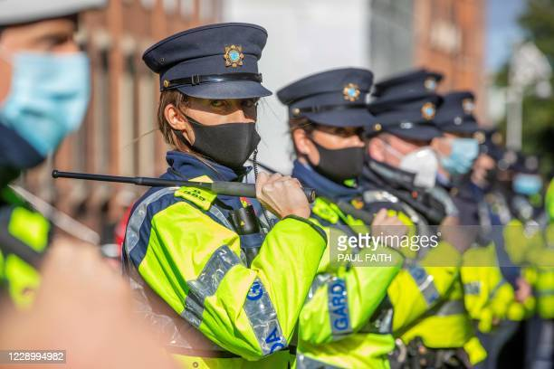 Garda stand with batons drawn to keep counter-protestors from protestors staging a demonstration against the Irish government imposed restrictions...