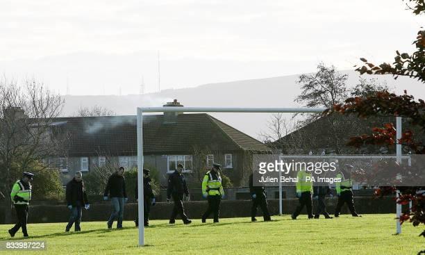 Gardai officers search a field near the scene of last night's fatal stabbing in a laneway off Beechfield Road in the Walkinstown area of Dublin