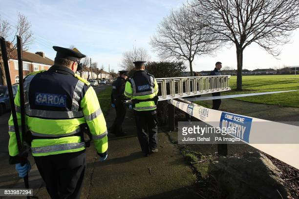 Gardai officers search the area around the scene of last night's fatal stabbing in a laneway off Beechfield Road in the Walkinstown area of Dublin