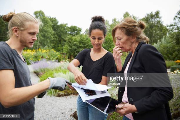 Garden architects with blueprints and digital tablet discussing in garden