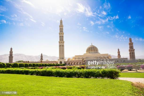 garden by mosque in city against blue sky - muscat governorate stock pictures, royalty-free photos & images