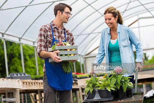 Garden center employee assists female customer