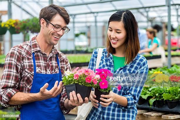 Garden center employee sells flowers to customer