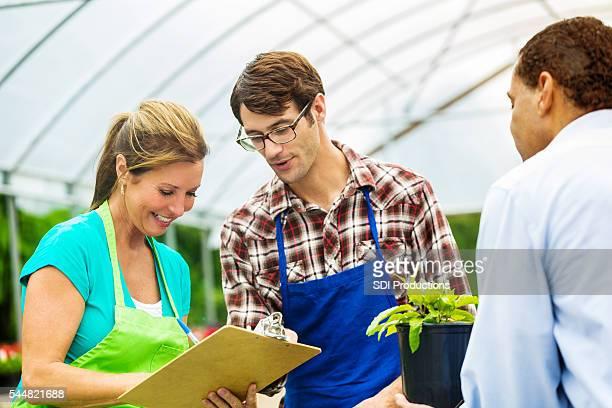 Garden center employees writing up a purchse for a customer