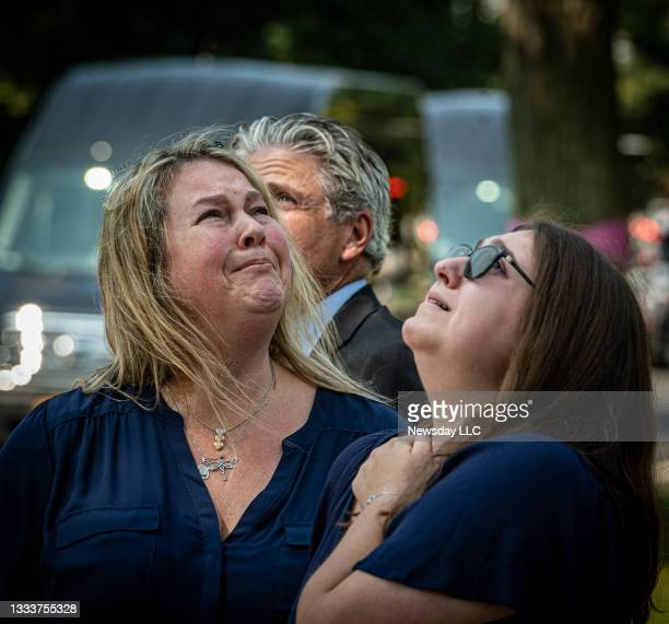After funeral services for Nassau County Police officer Matthew Perlungher in Garden City, New York, his wife Erika and daughter Emma look skyward at...