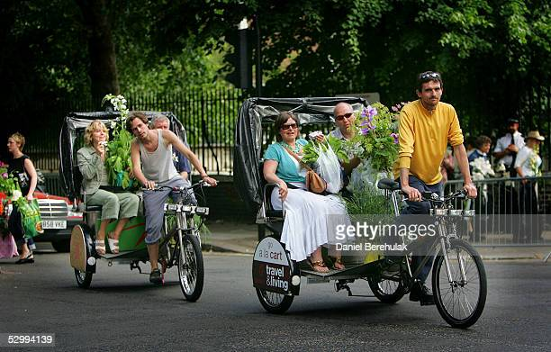Garden enthusiasts catch rickshaws to transport their purchases home during the last day of the Royal Horticultural Society's Chelsea Flower Show on...