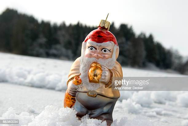 Garden gnome figurine on snow, close up