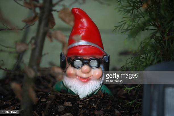 Garden gnome wearing sunglasses and headphones lies partially buried under a hedge in an apartment complex courtyard on February 1, 2018 in Berlin,...