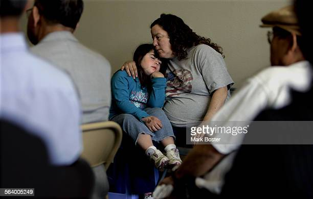 –Garden Grove resident Lori English holds her daughter Haley Daugherty at a meeting with local citizens concerned about the pharmacy closings English...