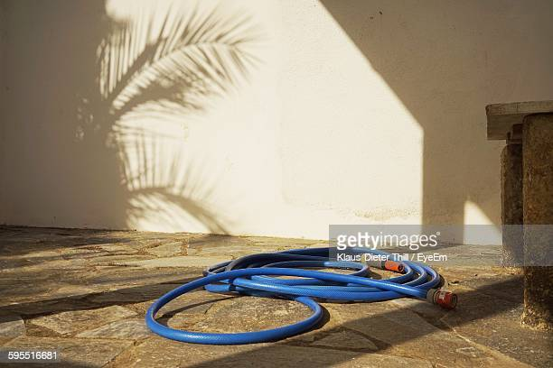 Garden Hose Against Wall During Sunny Day