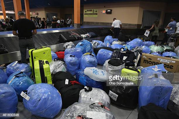 Garden of luggage and goods, wrapped in plastic to protect against tampering and theft, cover the baggae claim area at Jose Marti International...