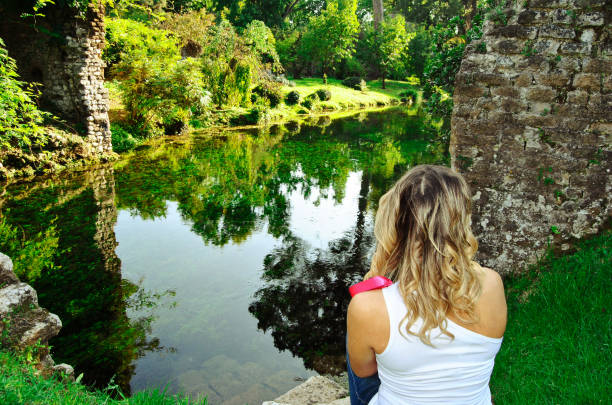 Garden Of Ninfa - Rear View Of Blonde Woman Looking At The River