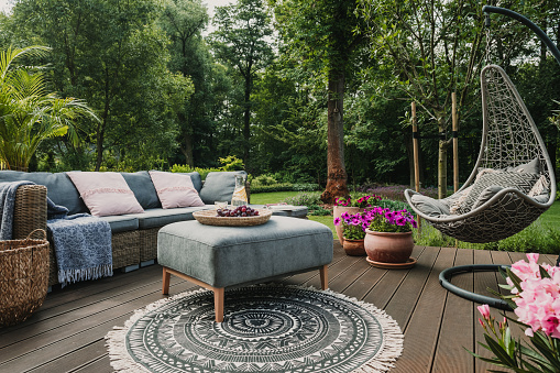 Garden patio decorated with Scandinavian wicker sofa and coffee table 1208657520