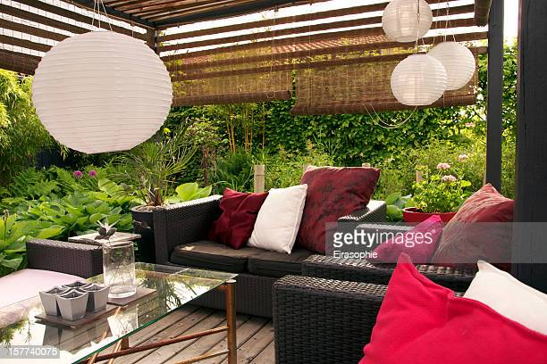 A garden patio with wicker sofas surrounded by trees