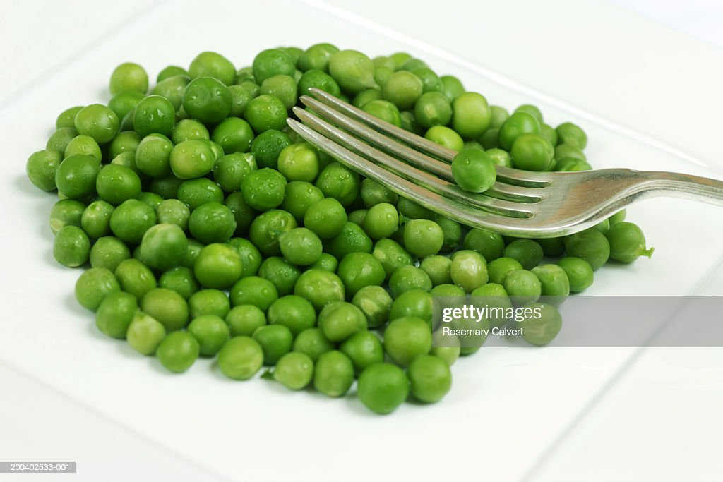 garden peas and fork on plate close up stock photo - Garden Peas