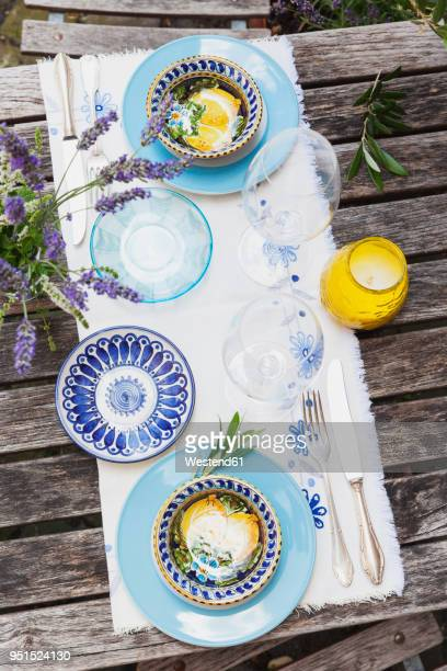 Garden table laid with colorful plates and bowls