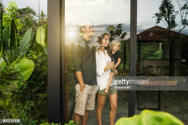 garden view of parents with their young son looking outside of their design house surrounded by lush tropical garden - wealth stock pictures, royalty-free photos & images