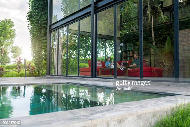 garden view through glass facade of couple with laptop and book relaxing on red couch in modern design house in front of swimming pool - premium access stock pictures, royalty-free photos & images