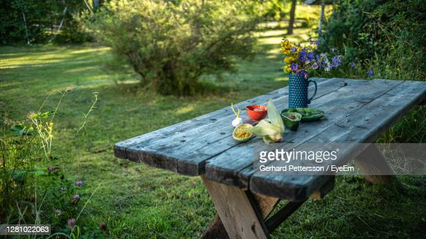 garden with wooden table of old planks in the country with flowers - picnic table stock pictures, royalty-free photos & images