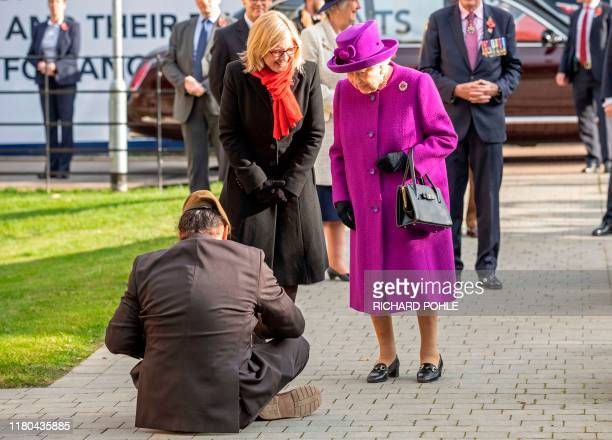 Gardener and veteran John Ahben from Fiji gives a traditional Fijian welcome to the Queen by sitting on the floor in front of her as she arrives at...