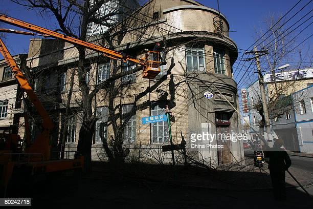 Gardener cut the branches beside a building built during the Japanese occupation of Manchuria on March 13, 2008 in Changchun of Jilin Province,...