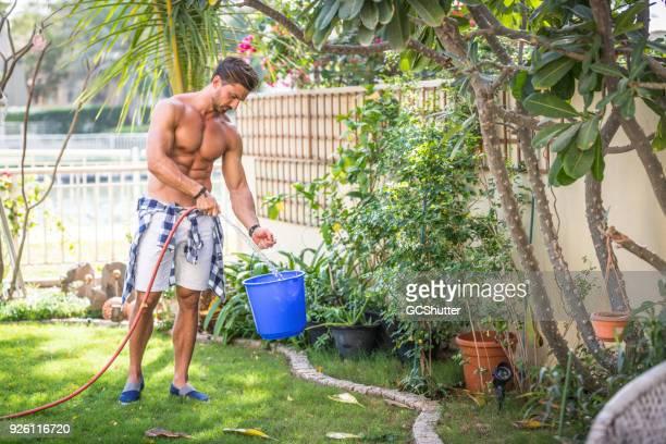Gärtner seinen Eimer mit Wasser füllen