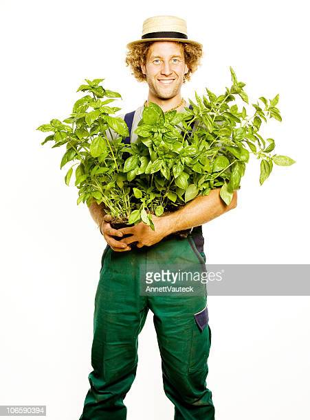 A gardener holding some pots of plants in his arms