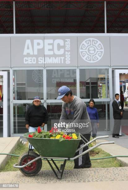 A gardener places flowers outside the CEO's conference centre on November 18 2008 in the Defense Ministry in Lima during preparations for the...