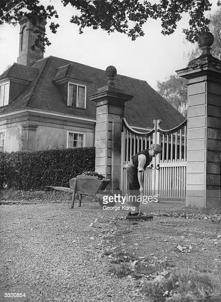 A gardener rakes leaves away from the gate of a country house on Windlesham Moor Surrey