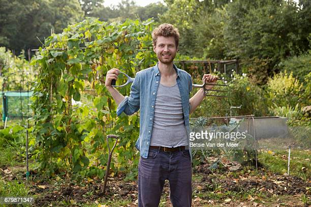 gardener standing in allotment with garden tool. - green fingers stock pictures, royalty-free photos & images
