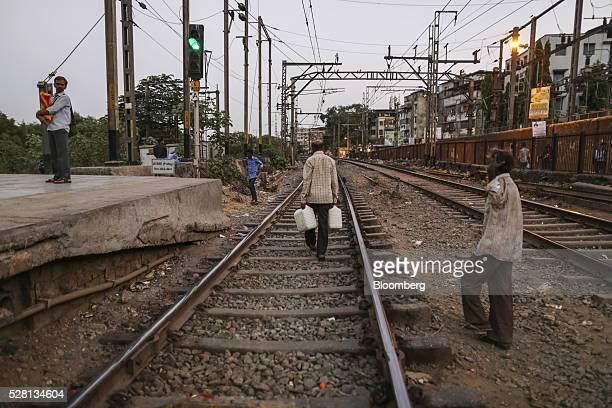 Gardener Vishwas Bhosale carries water cans along train tracks at Mumbra railway station in Mumbai, India, on Sunday, April 17, 2016. Hundreds of...