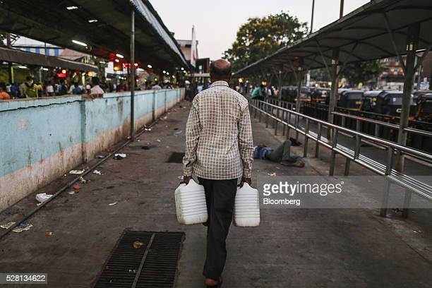 Gardener Vishwas Bhosale carries water cans outside Mumbra railway station in Mumbai, India, on Sunday, April 17, 2016. Hundreds of millions of...