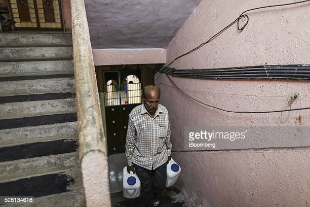 Gardener Vishwas Bhosale carries water cans up a flight of stairs at his home in Mumbai, India, on Sunday, April 17, 2016. Hundreds of millions of...