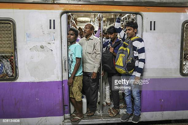 Gardener Vishwas Bhosale, second left, stands with water cans at the door of a train carriage at Diva railway station in Mumbai, India, on Sunday,...