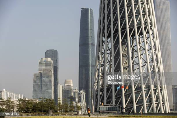 A gardener waters the lawn in front of the residential and commercial buildings including the Canton Tower right in Guangzhou China on Wednesday Nov...