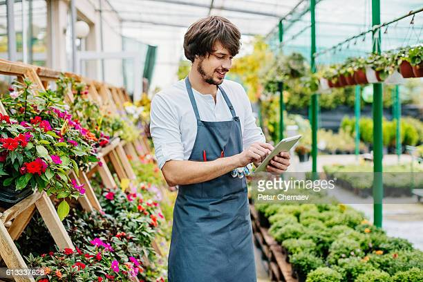 Gardener with digital tablet in a greenhouse