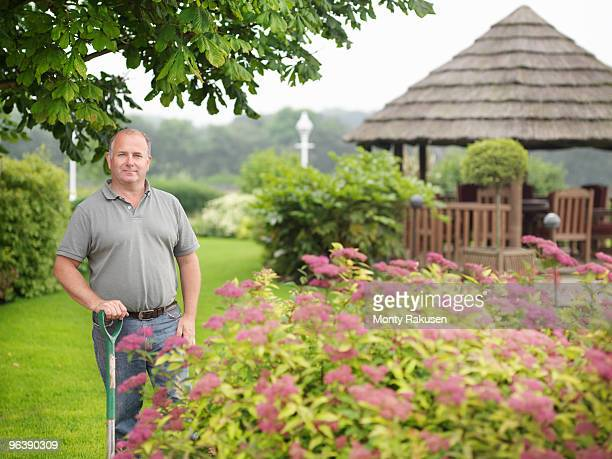 gardener with spade in garden - ground staff stock pictures, royalty-free photos & images
