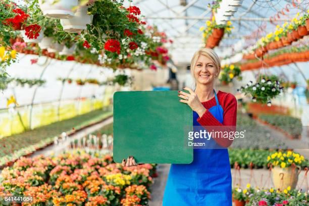 Gardener - woman holding blackboard in plant nursery and smiling