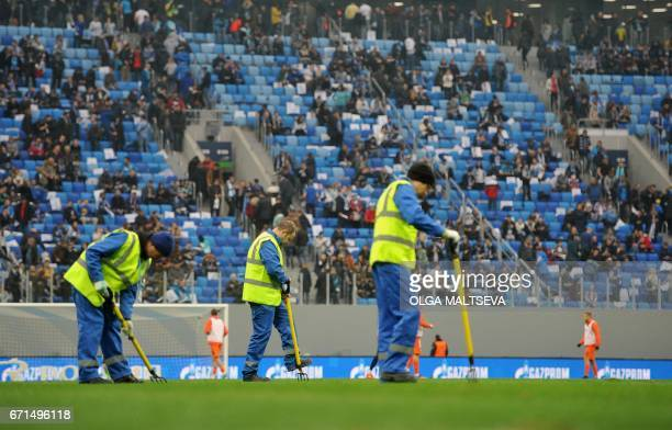 Gardeners maintain the lawn during the Russian League football match between FC Zenit and FC Ural at the new 'Saint Petersburg' football stadium also...