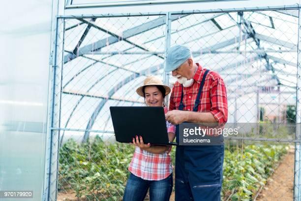 Jardineros con el portátil delante de invernadero