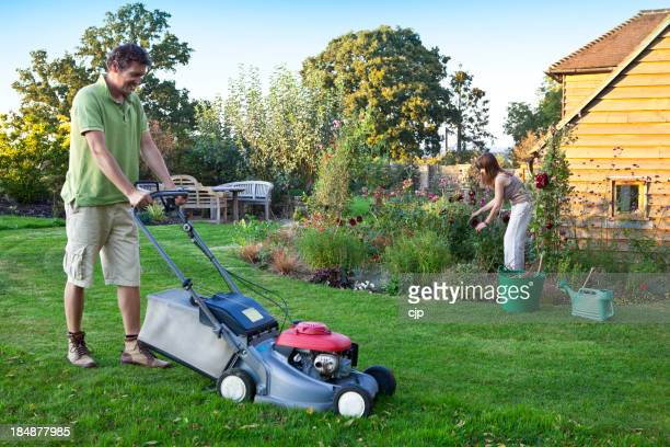 Gardening Couple Mowing and Pruning
