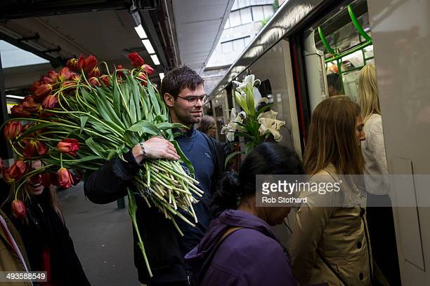 A gardening enthusiast boards a London Underground District Line train with flowers purchased on the final day of the Chelsea Flower Show at Royal...