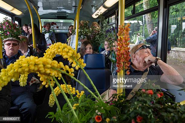 Gardening enthusiasts board a bus with flowers purchased on the final day of the Chelsea Flower Show at Royal Hospital Chelsea on May 24 2014 in...