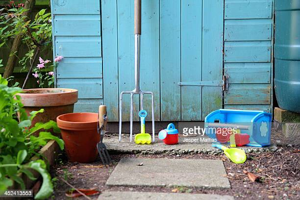 Gardening tools, pots and toys outside shed