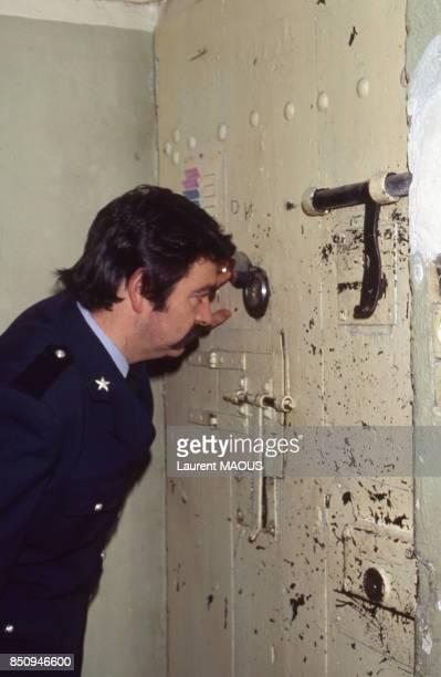 Gardien de prison regardant dans un oeilleton à la prison de Perpignan France le 25 mars 1984