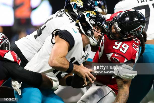 Gardner Minshew II of the Jacksonville Jaguars is brought down by Grady Jarrett and Adrian Clayborn of the Atlanta Falcons during the first half of a...