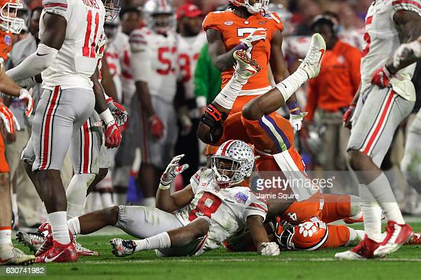 Gareon Conley of the Ohio State Buckeyes upends Deshaun Watson of the Clemson Tigers during the second half of the 2016 PlayStation Fiesta Bowl at...
