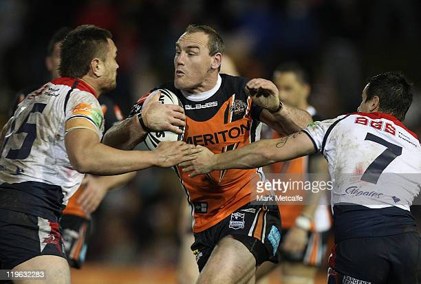 Garerth Ellis of the Tigers is tackled during the round 20 NRL match between the Wests Tigers and the Sydney Roosters at Leichhardt Oval on July 23...